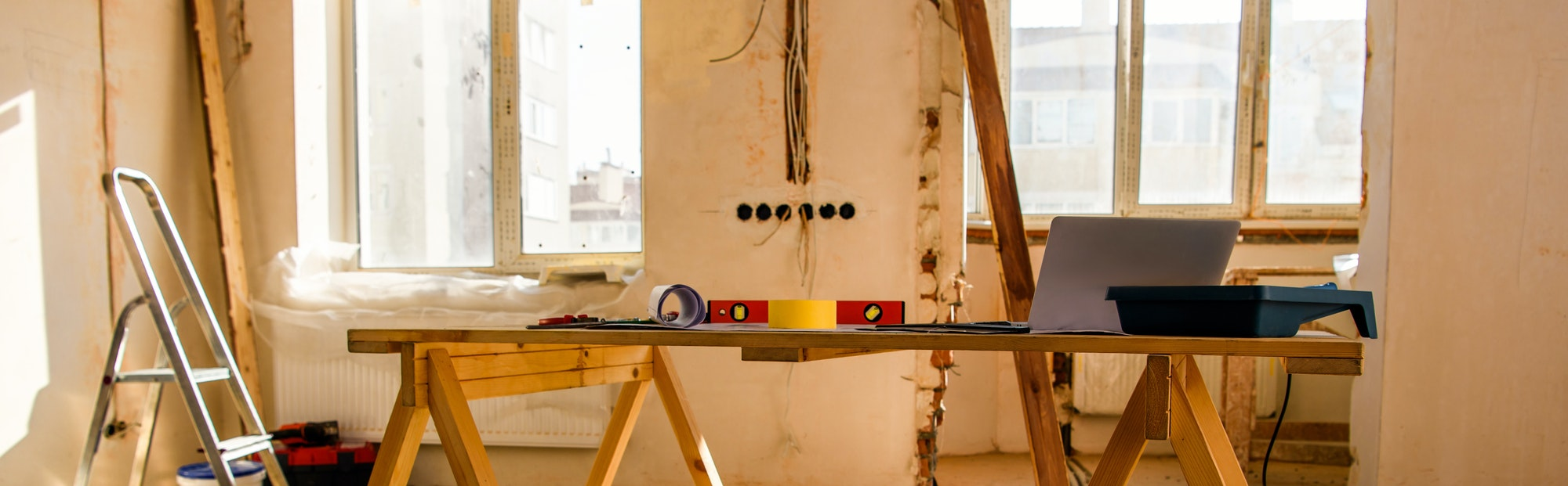 panoramic view of room with tools, ladder and laptop during renovation of home
