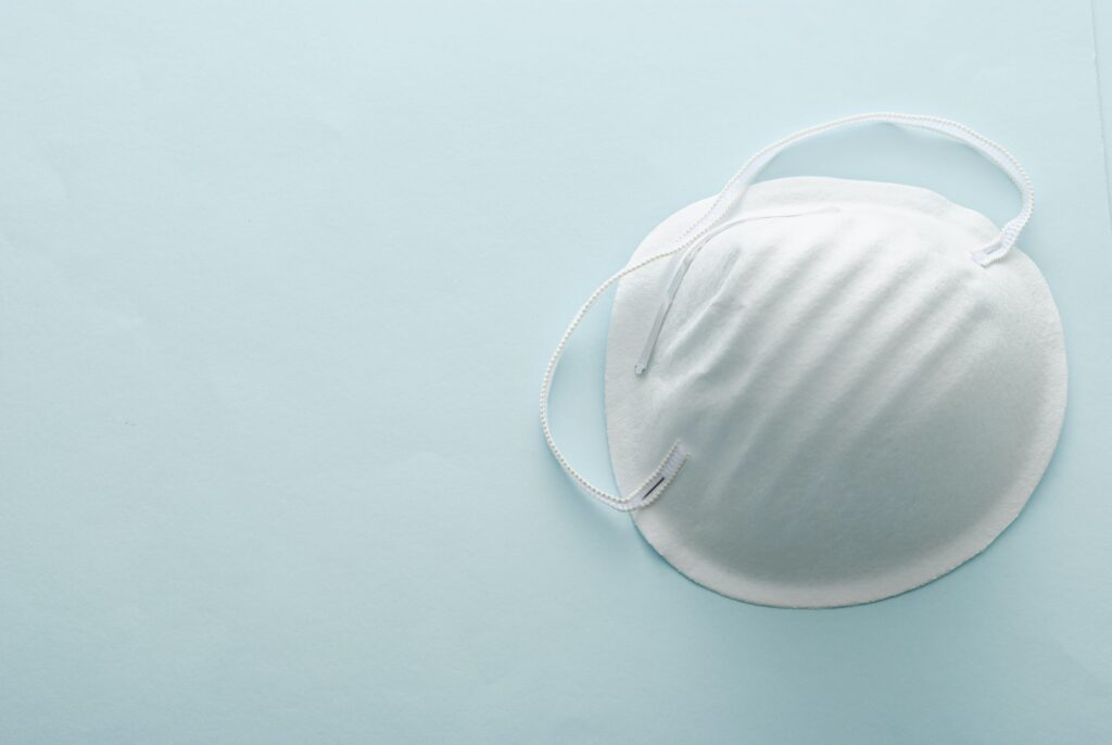 Single surgical face mask on a grey background